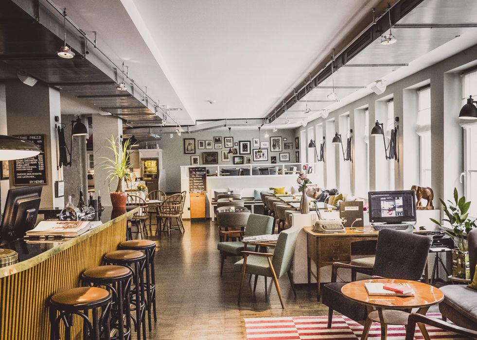 Het restaurant in zachte tinten, bar met barkrukken, hoge ramen