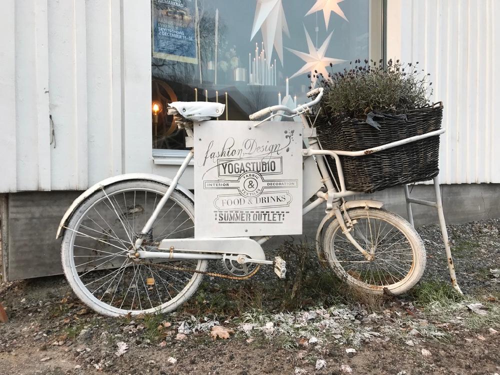 Een witte fiets met een uithangbord voor een yogastudio