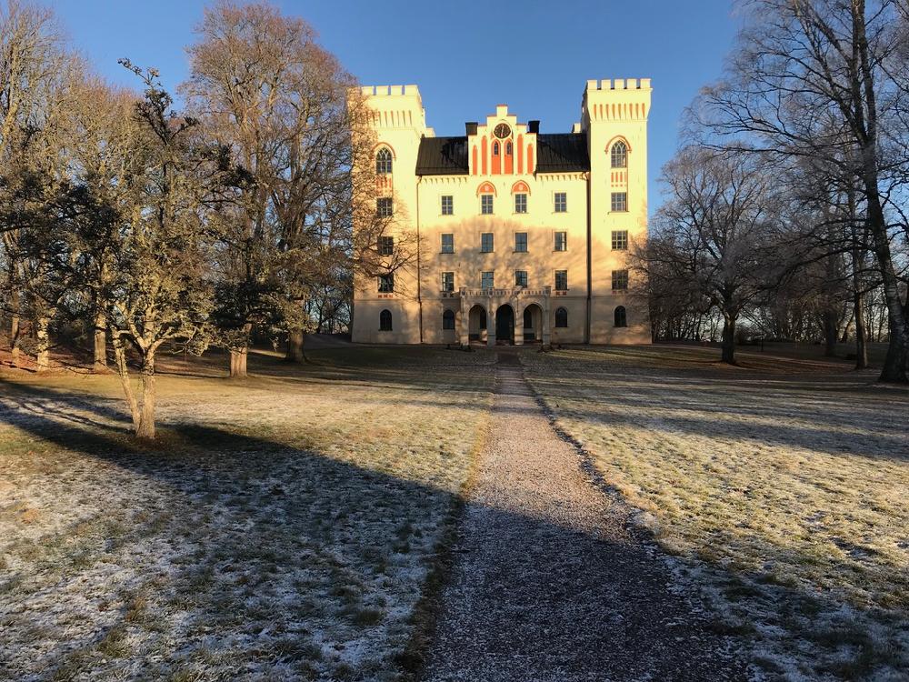 Een bevroren oprijlaan met een geel kasteel met twee torens