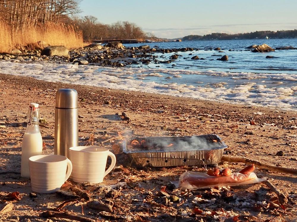 Wegwerp BBQ op het strand, met bevroren waterkant, een thermosfles en twee witte mokken