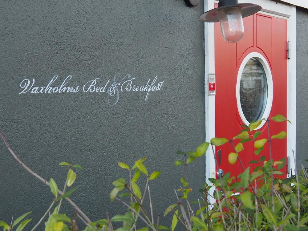 Zwarte muur met de tekst van de B&B Vaxholm en een rode deur