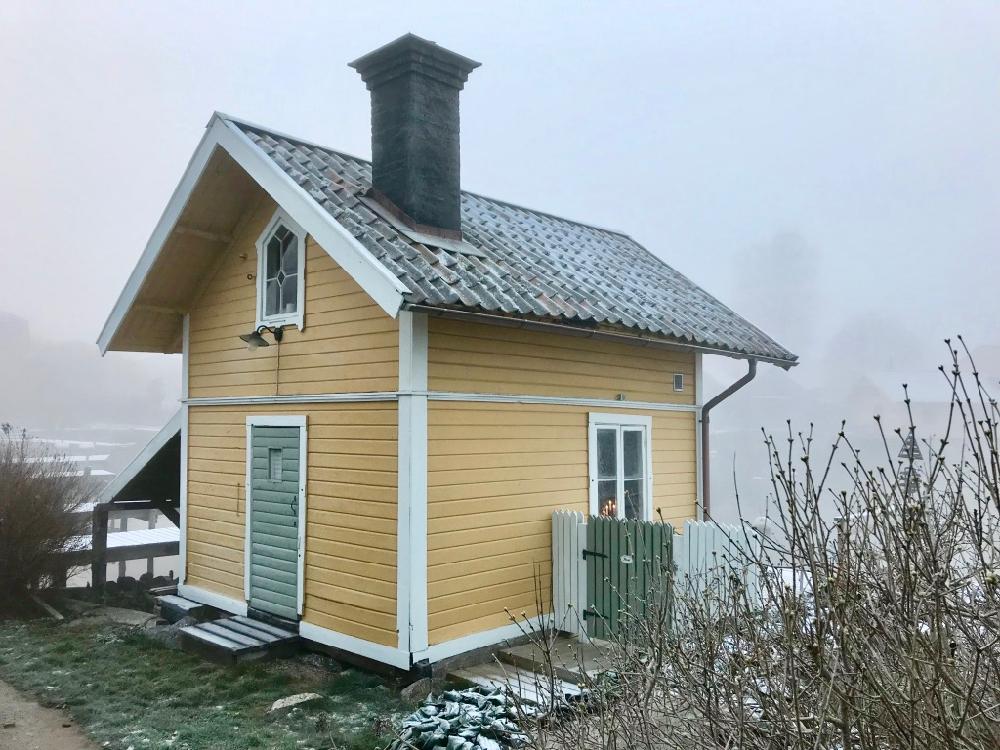 Een geel houten huisje op het Zweedse eiland Vaxholm, met een laagje rijp bedekt.