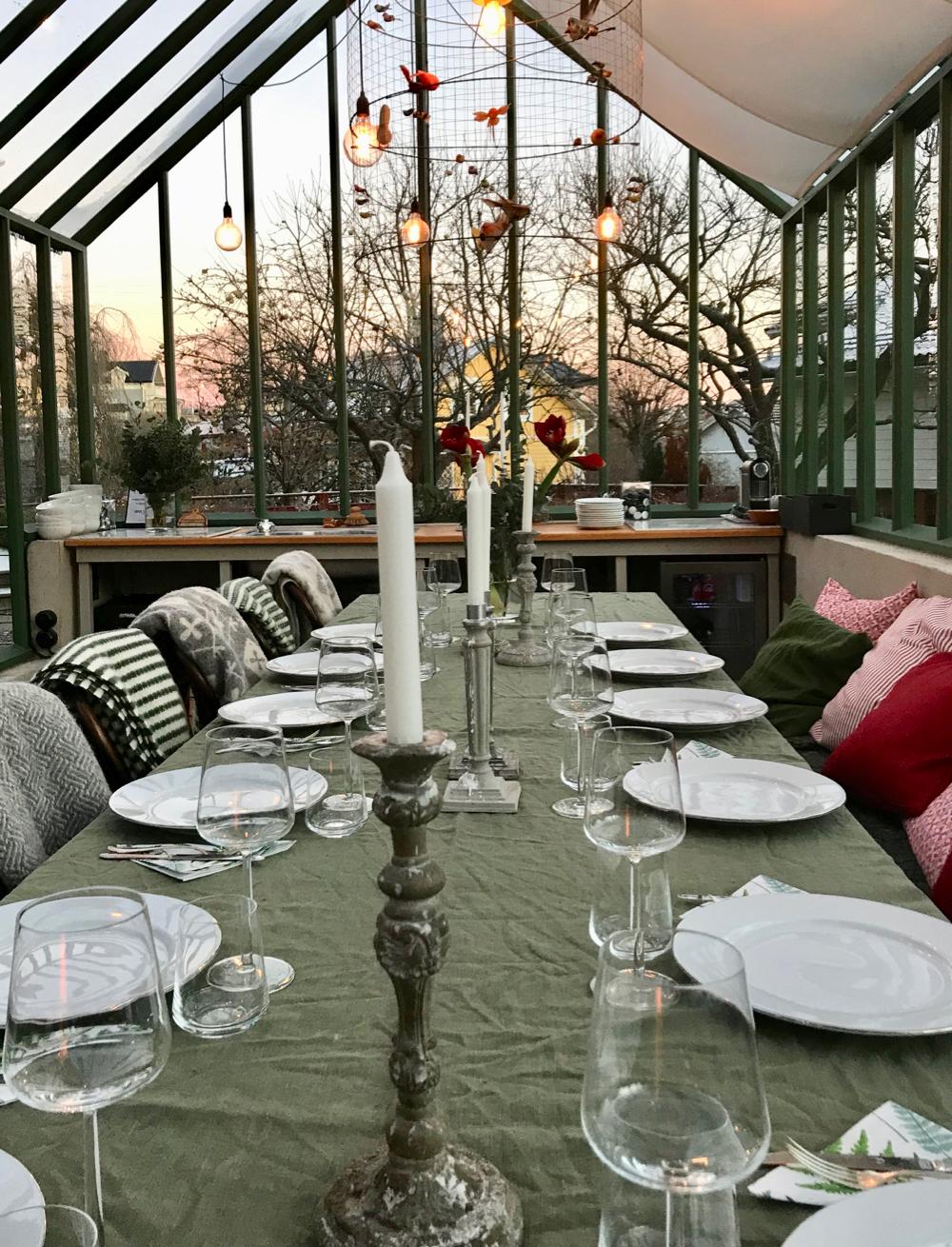 Een gedekte tafel in een kas met kaarsen, in de tuin van Vaxholms B&B