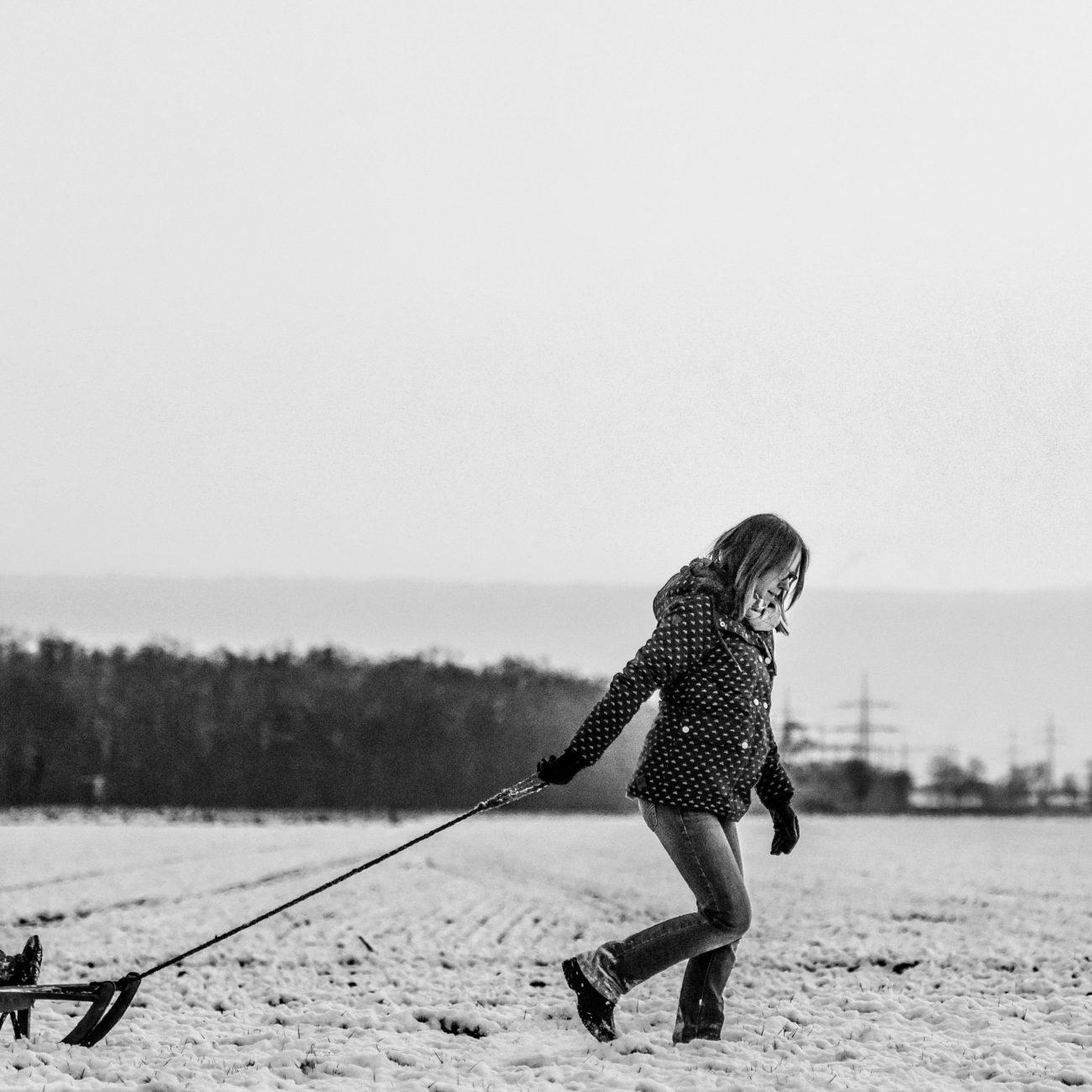 Zwart wit foto van een moeder die haar kindje voortrekt op de slee