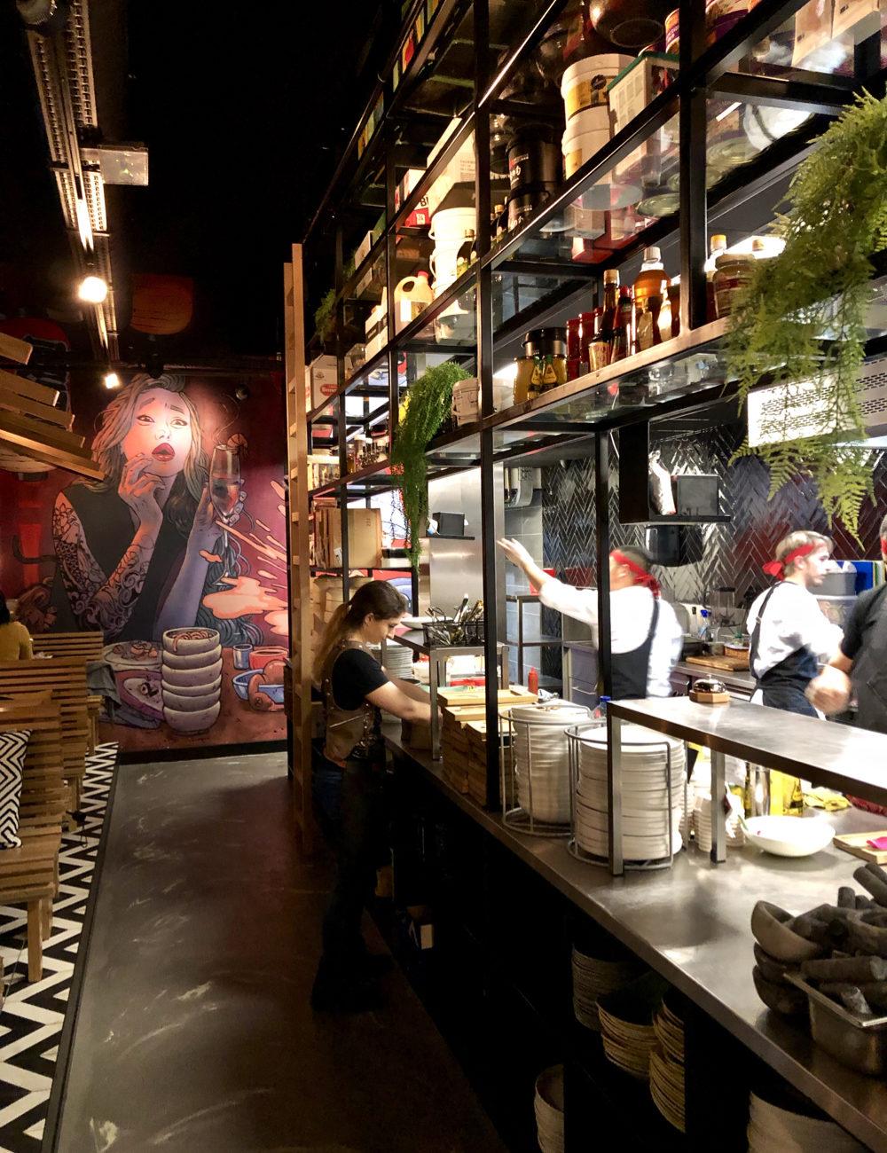 Een stoere open keuken met zwart metaal, een grote wandschildering en Japanse koks aan het werk