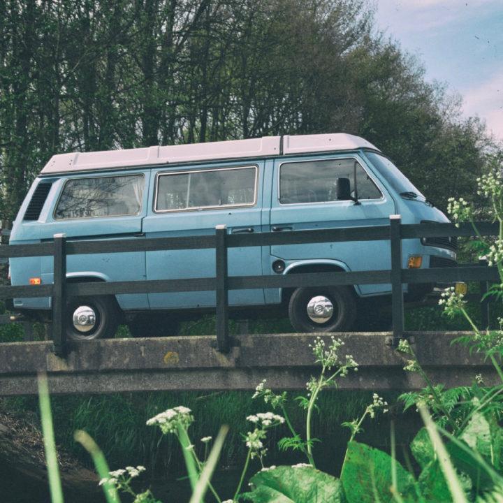 Blauw Volkswagen camperbusje op een brug
