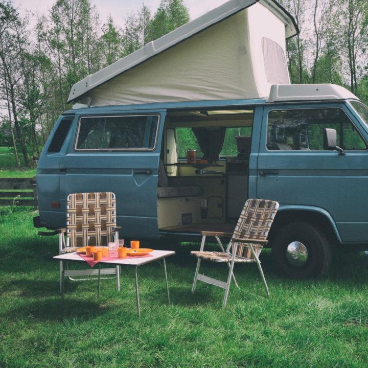 Camper met opstaand dak, en tafel met stoeltjes ervoor in het gras