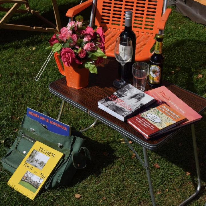 Tafeltje met boeken, een flesje wijn en tips voor de Achterhoek