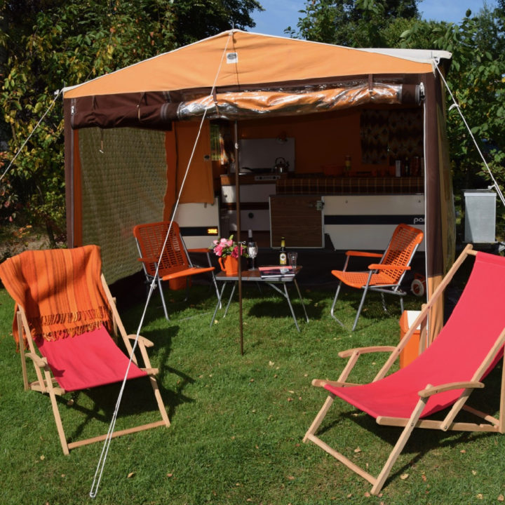 Ouderwetse vouwwagen met oranje luifel en rode strandstoelen