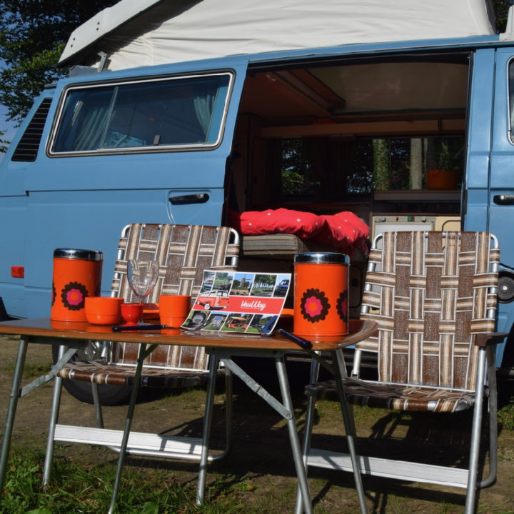 Retro tuinstoeltjes voor een blauwe camper