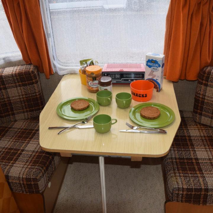 Gedekte tafel in een caravan, ouderwetse kussens en oranje gordijnen