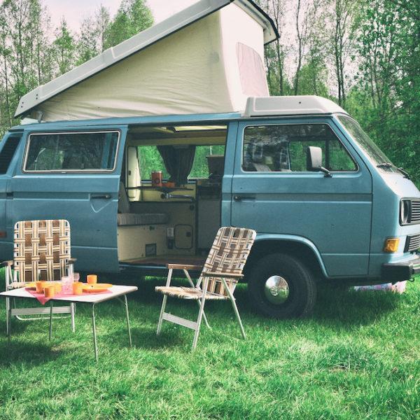 Blauwe Volkswagen camper, in het gras met vintage stoelen ervoor