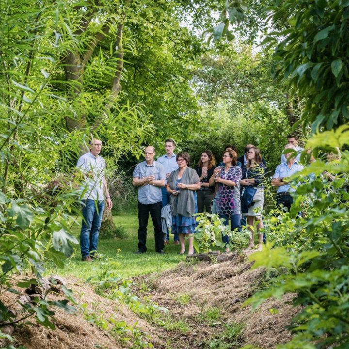 Een groep mensen krijgt een rondleiding door het voedselbos