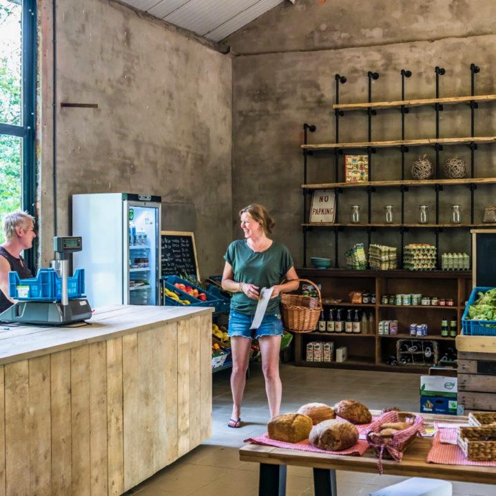 Winkel met steigerhouten toonbank, broden en stoere schappen langs de muur