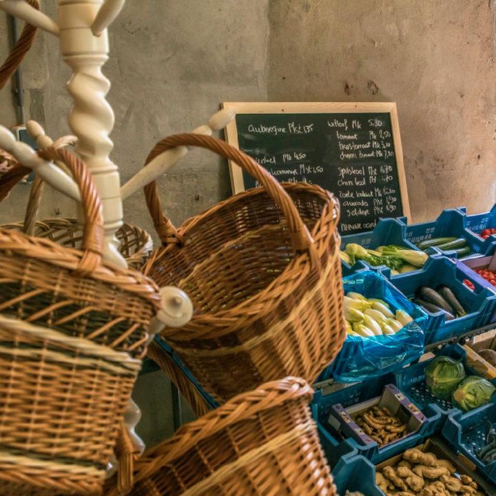 Rieten manden aan een kapstok, groente in blauwe bakken