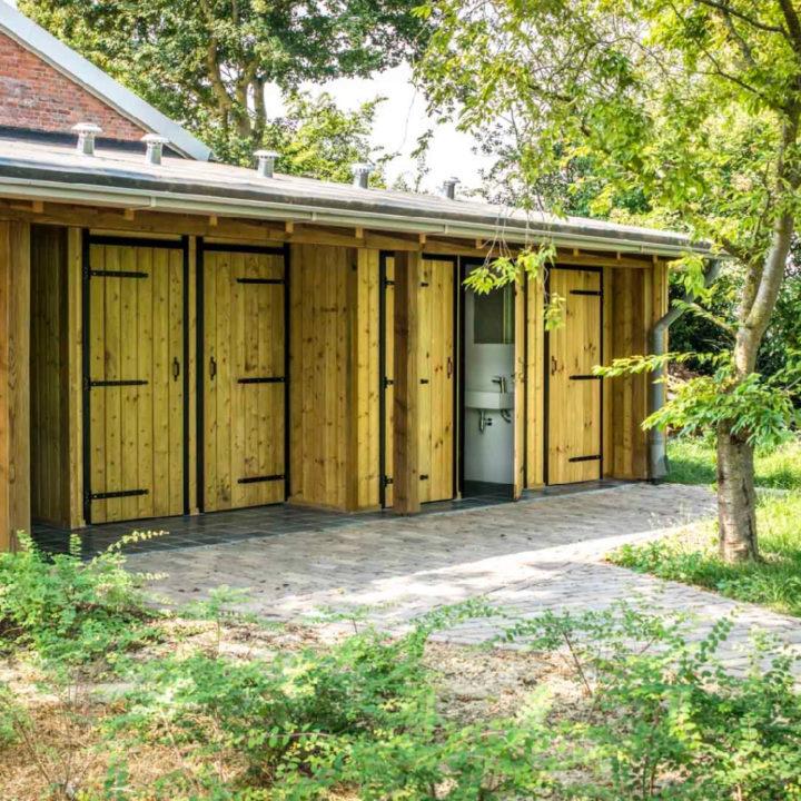Houten sanitairgebouw met bomen eromheen