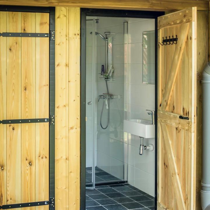 Nieuw sanitairgebouw met moderne douche en houten deuren