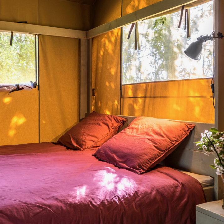 Tweepersoons opgemaakt bed in een safaritent bij Voedselbron Graauw