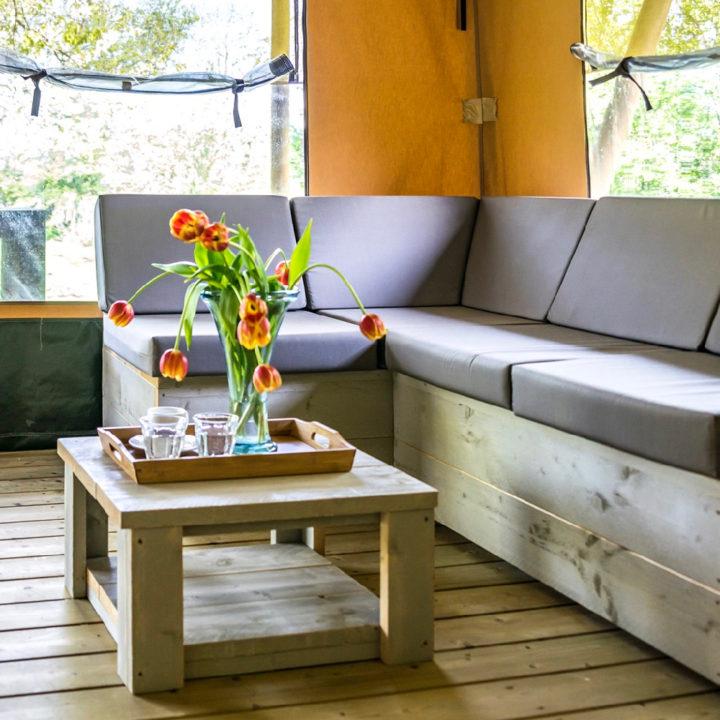 Loungebank met grijze kussens en een tafel met bos tulpen