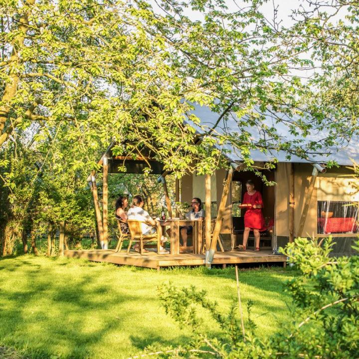 Safaritent tussen de bomen met mensen aan tafel op de veranda