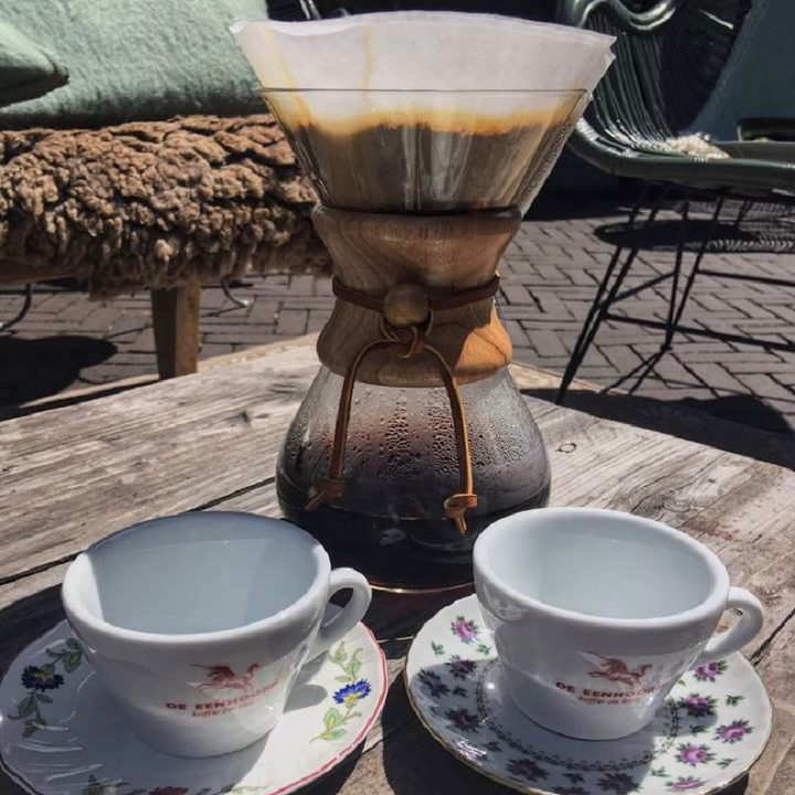 Twee koffiekopjes op een houten tafeltje, met pruttelende slow coffee