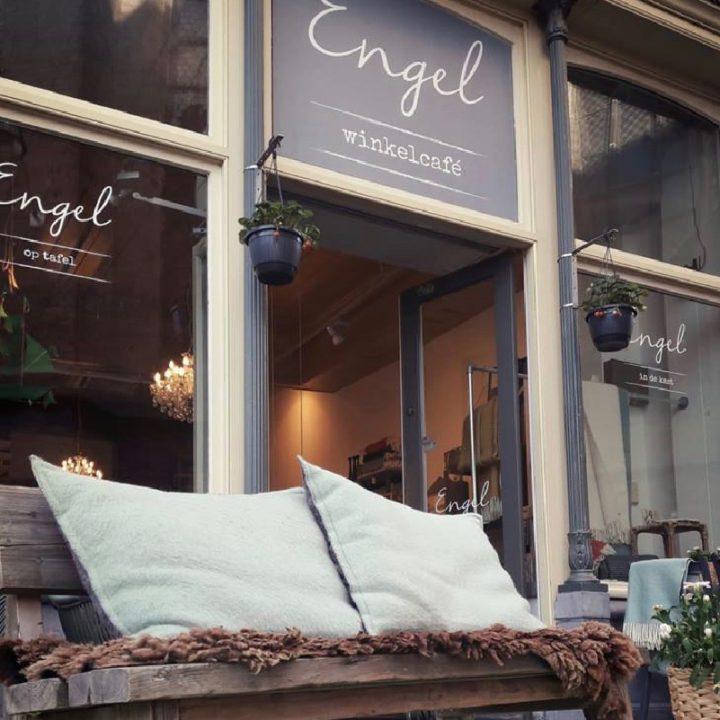 Houten bankje voor de gevel van Engel winkelcafe, met bruine schapenvacht