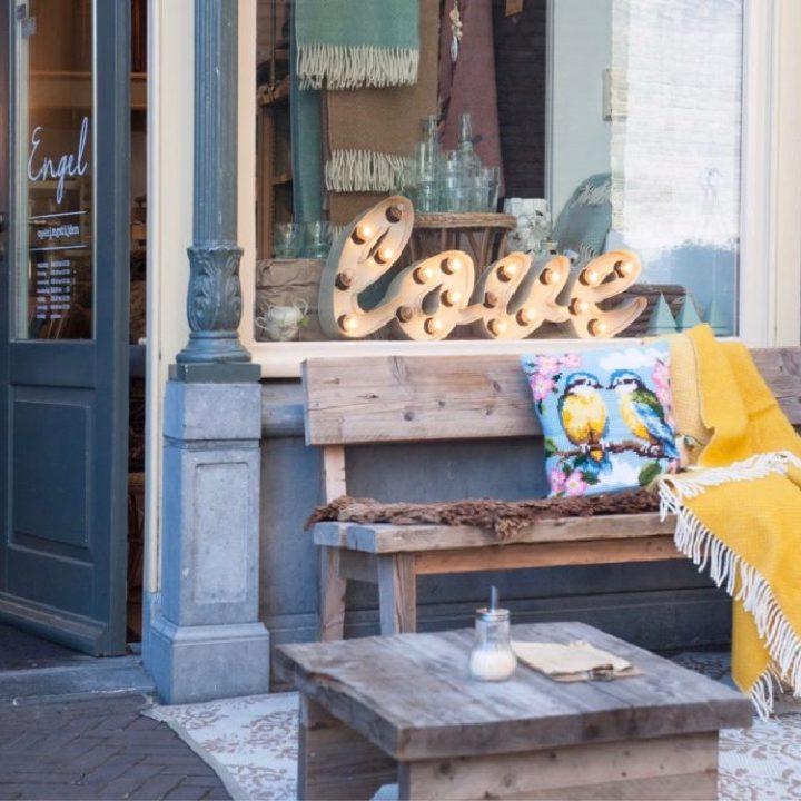 Houten bankje met vachtje, kussen en gele plaid