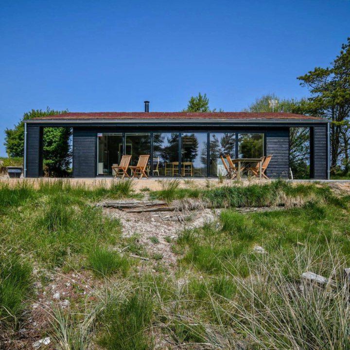 Gras met terras en zwart vakantiehuis