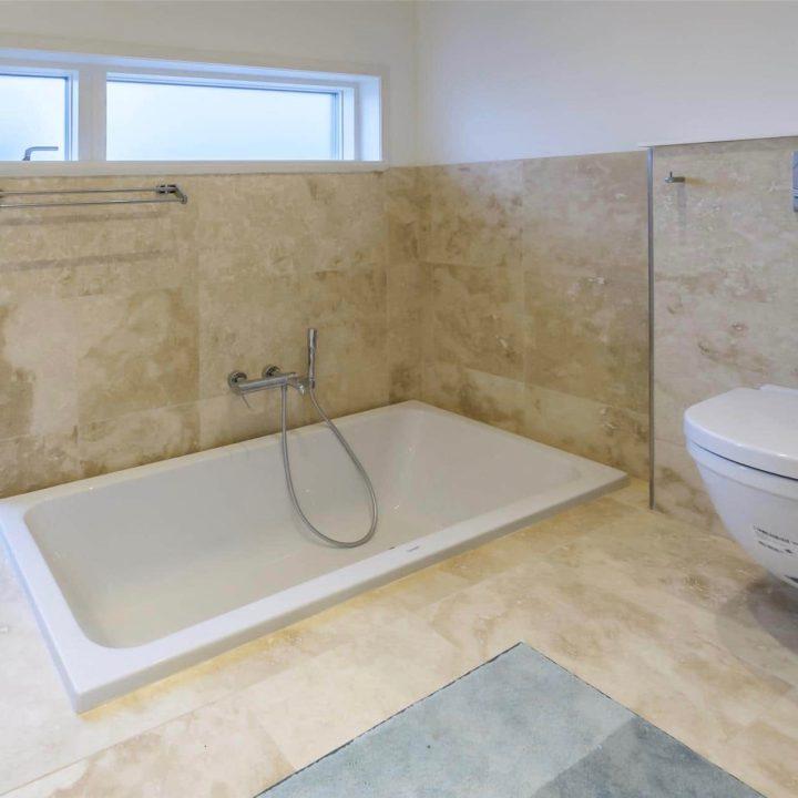 Badkamer met smal raam en ligbad in de grond