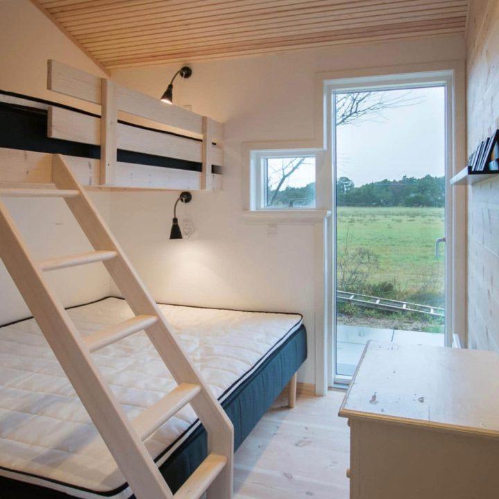 Slaapkamer met stapelbed en raam tot op de grond