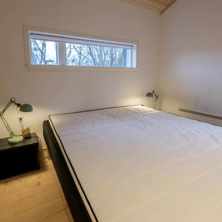 Slaapkamer met smal raam, tweepersoonsbed en twee groene bedlampen