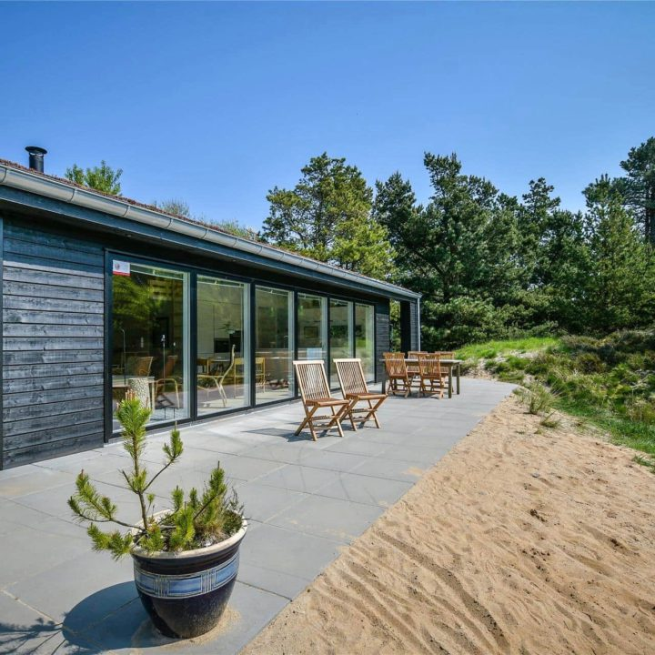 Terras met stoelen, een pot met een plant, omringd door bomen en met een zwart vakantiehuis