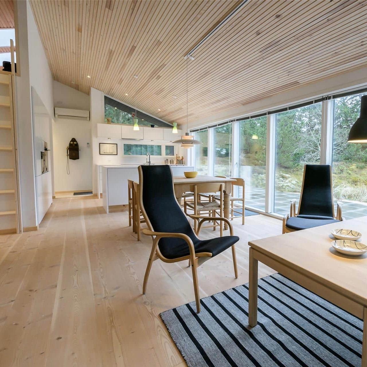 Doorkijk van zithoek naar eethoek en keuken, grote ramen tot op de grond