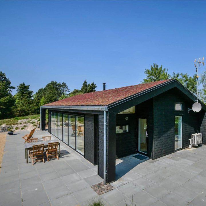 Zwart vakantiehuis met terrastegels eromheen