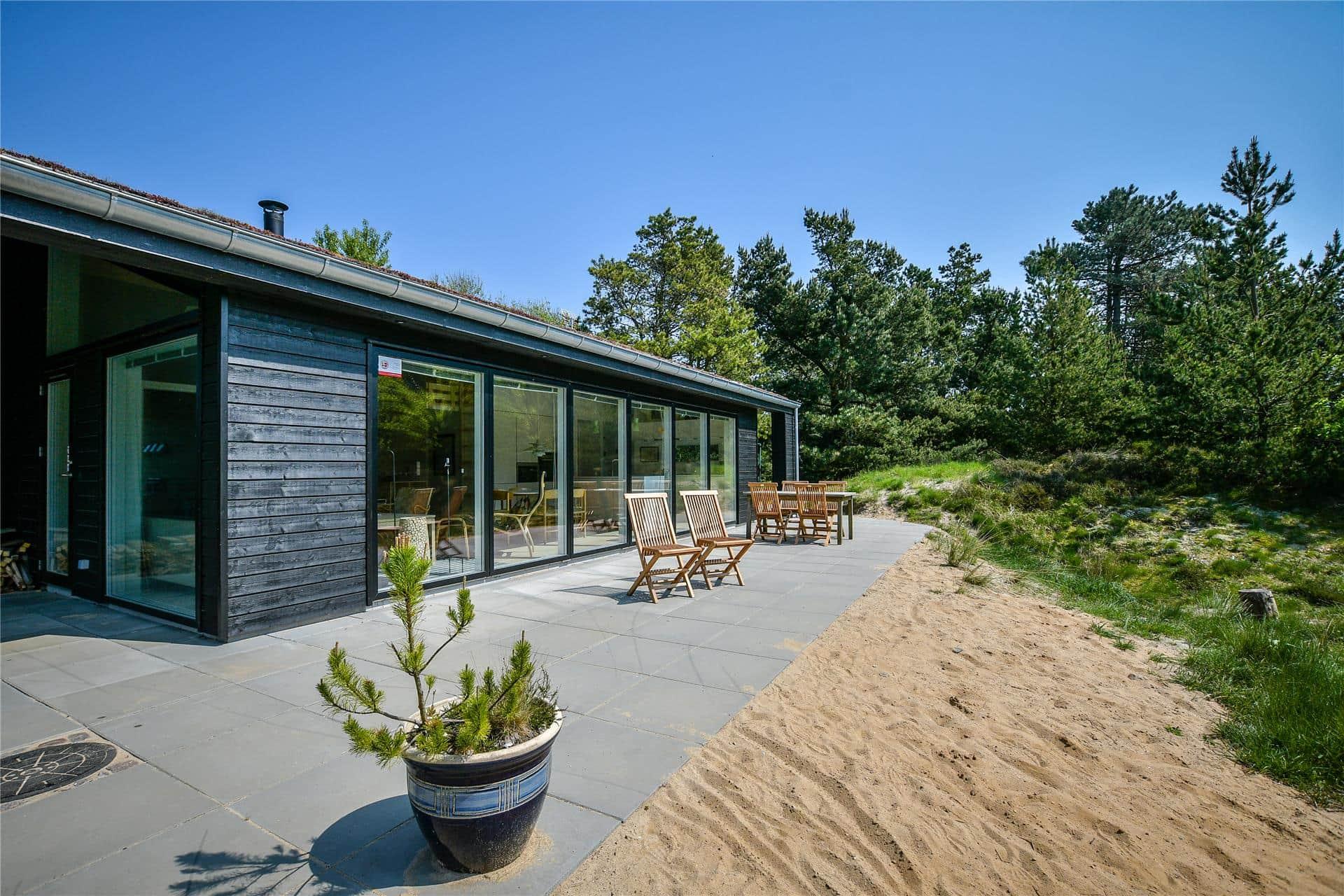 Zwart houten vakantiehuis met grote ramen en terras met houten stoelen