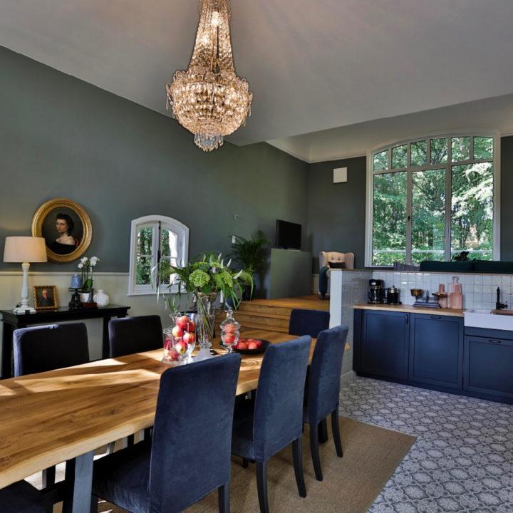 Eettafel met kroonluchter erboven en keuken met antraciet deurtjes