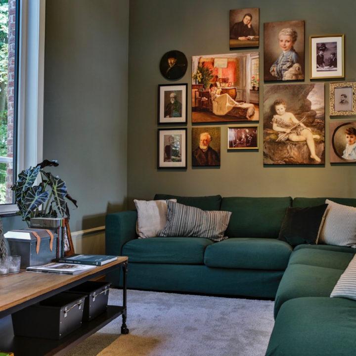 Zithoek met groene hoekbank, een salontafel en een verzameling schilderijen aan de wand