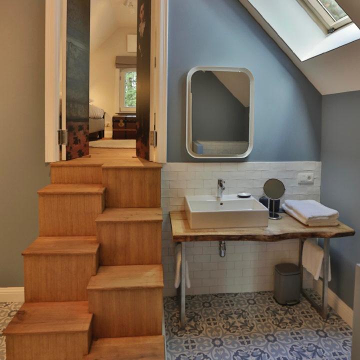 Badkamer met lichtlbauw grijze muur, houten trap naar slaapkamer
