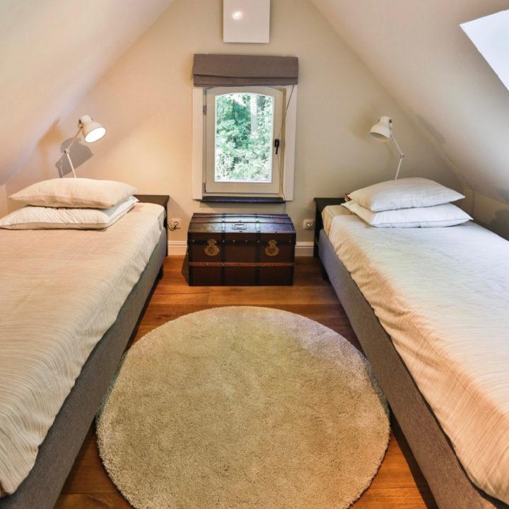Slaapkamer met twee aparte bedden, onder een schuin dak