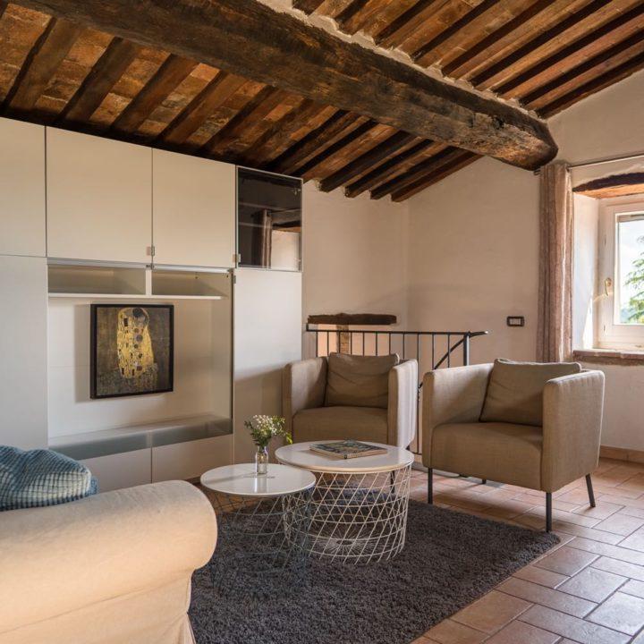 Authentiek balkenplafond, een stenen vloer en comfortabele fauteuils in beige