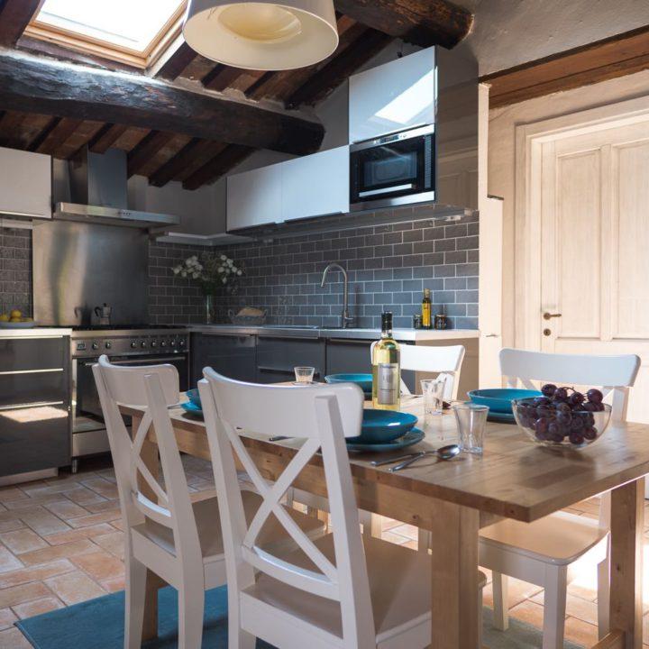 Eettafel met witte stoelen en antracietkleurige keuken op de achtergrond