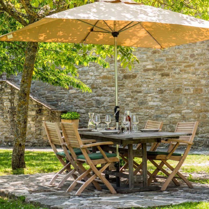 Gedekte tafel in de tuin, met parasol erboven