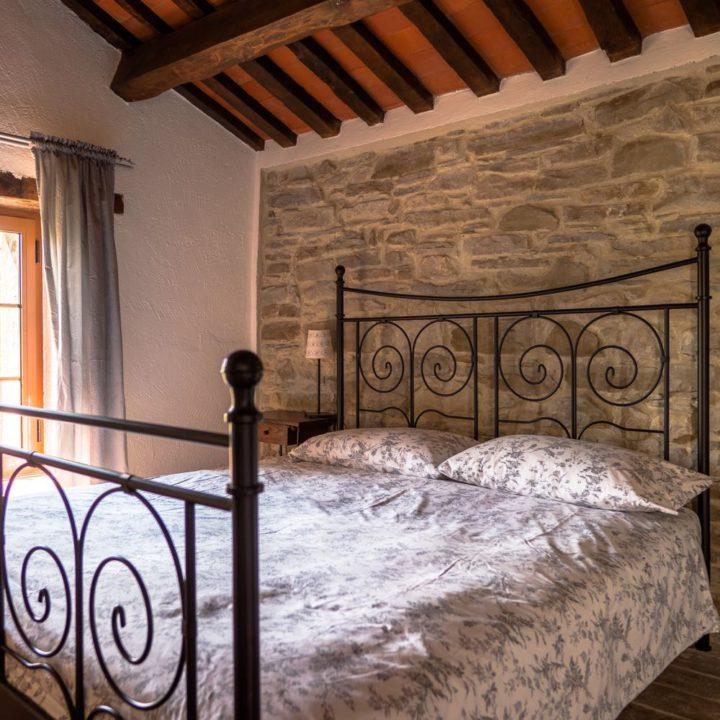 Een slaapkamer met tweepersoons spijlenbed en bloemetjes dekbed