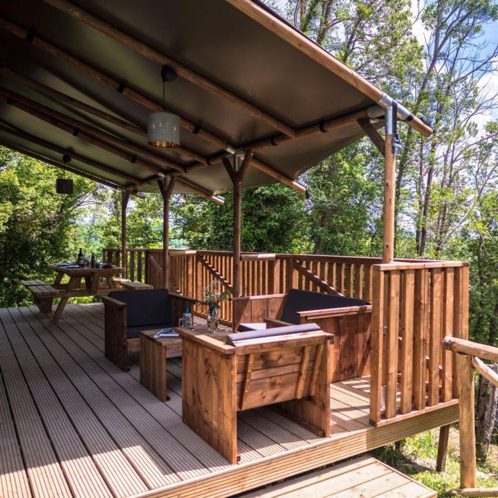 Overdekte veranda met ligstoelen en een picknicktafel
