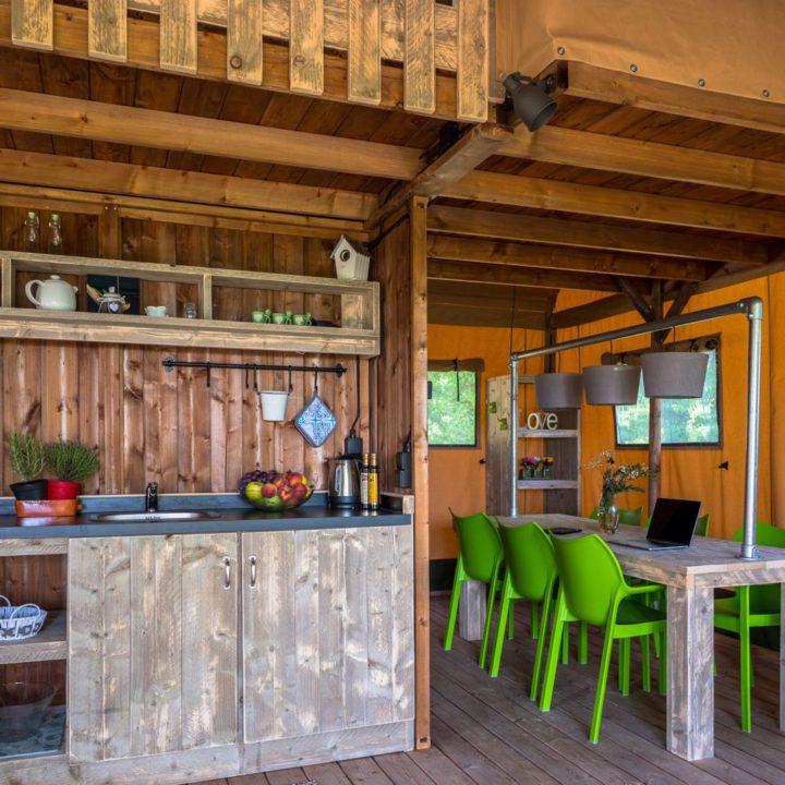 Robuust interieur van een safaritent met keukenblok en eettafel
