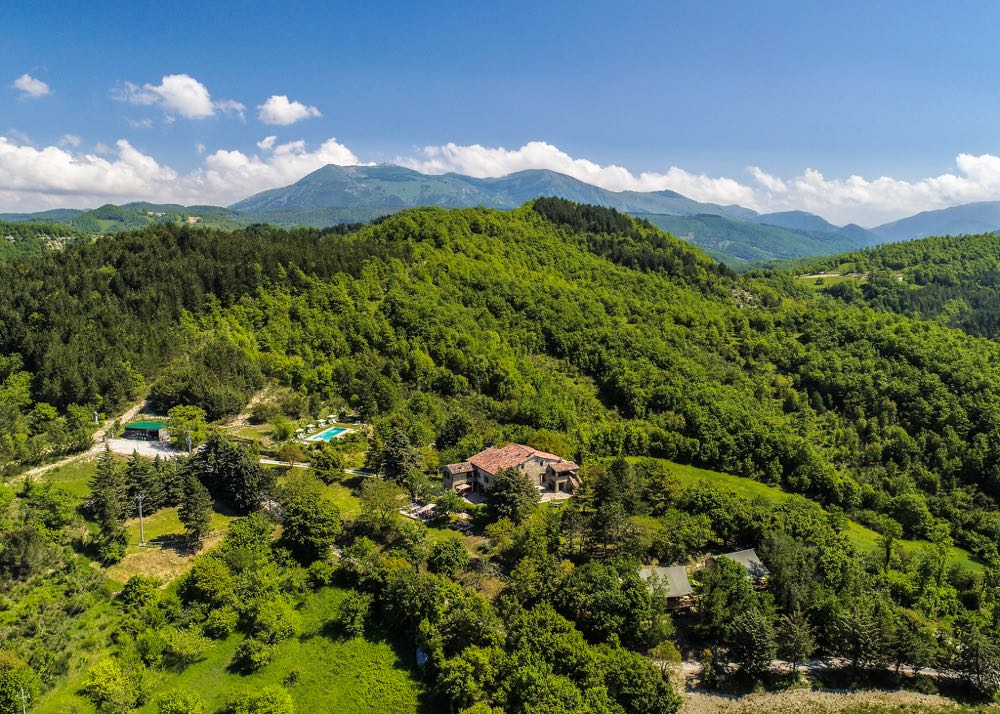 Groene heuvels met er tussen een zwembad, safaritenten en een Italiaans landhuis
