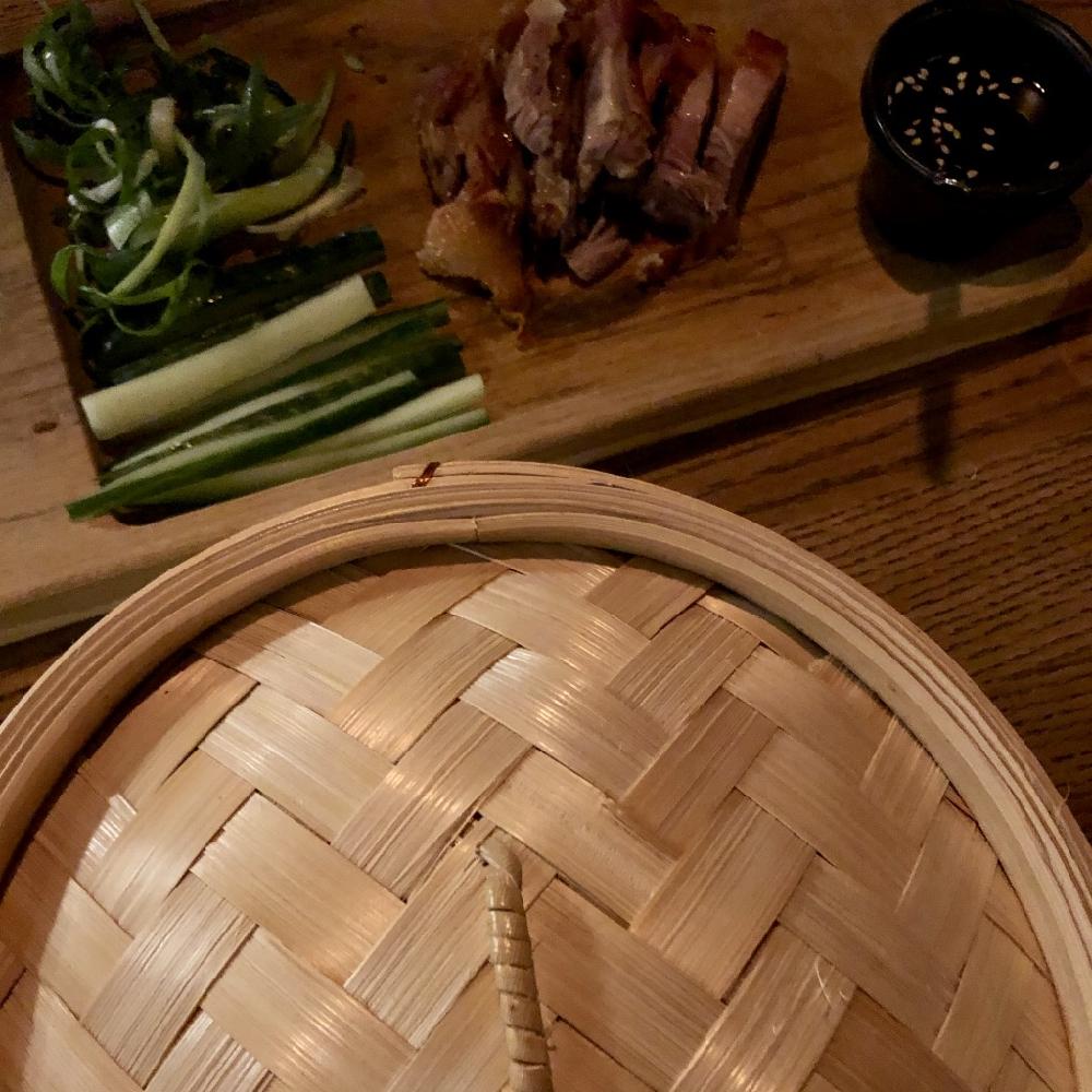Een rieten basket met een plankje ernaast met Peking Eend, bosui en saus