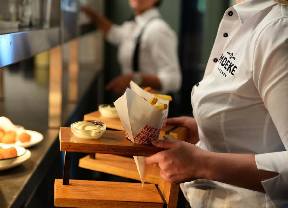 Serveerster met een witte puntzak friet in een houten standaard
