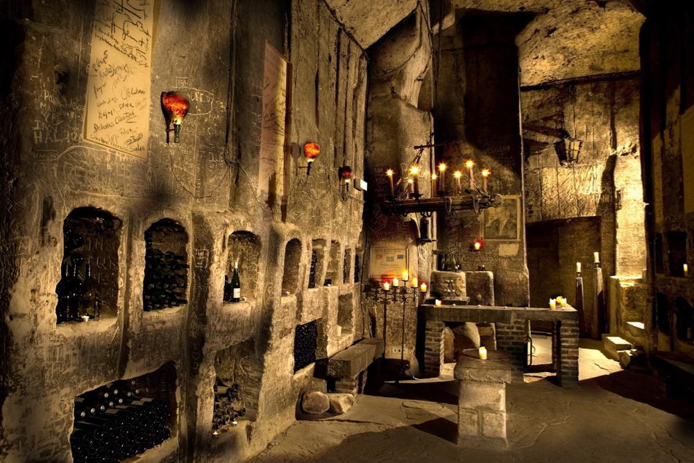 In de grotten onder het kasteel vind je de wijnkelder van Neercanne. Brandende kaarsen, flessen wijn