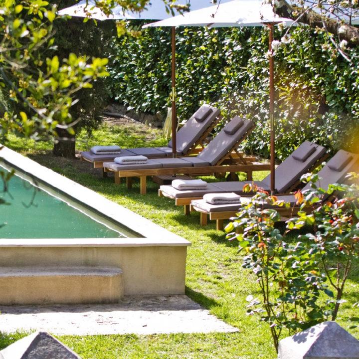 Een hoek van het zwembad met ligstoelen en parasols